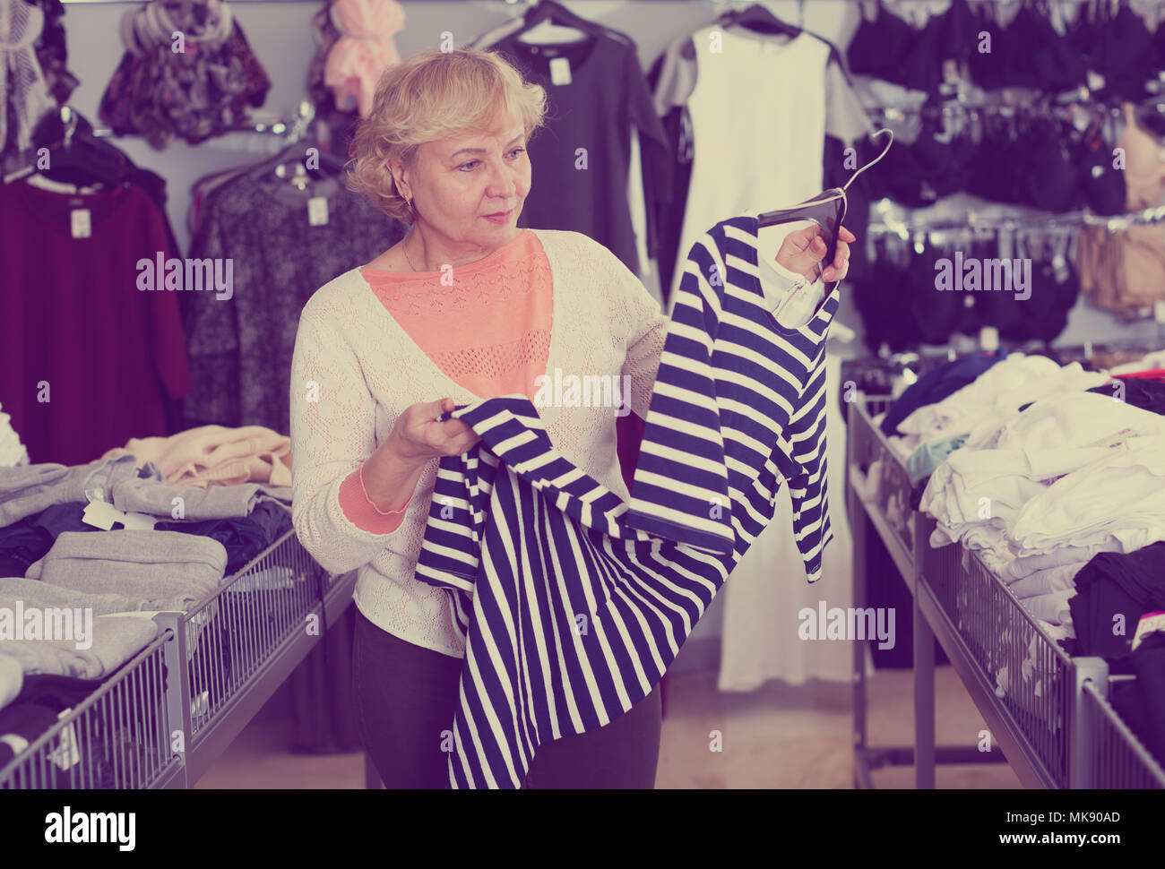 Adult woman purchaser choosing striped dress in the shopping center - Stock Image