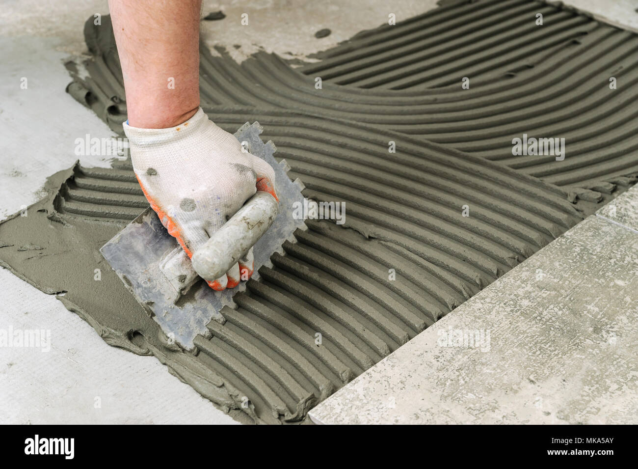 Laying Ceramic Tiles Troweling Mortar Onto A Concrete Floor In