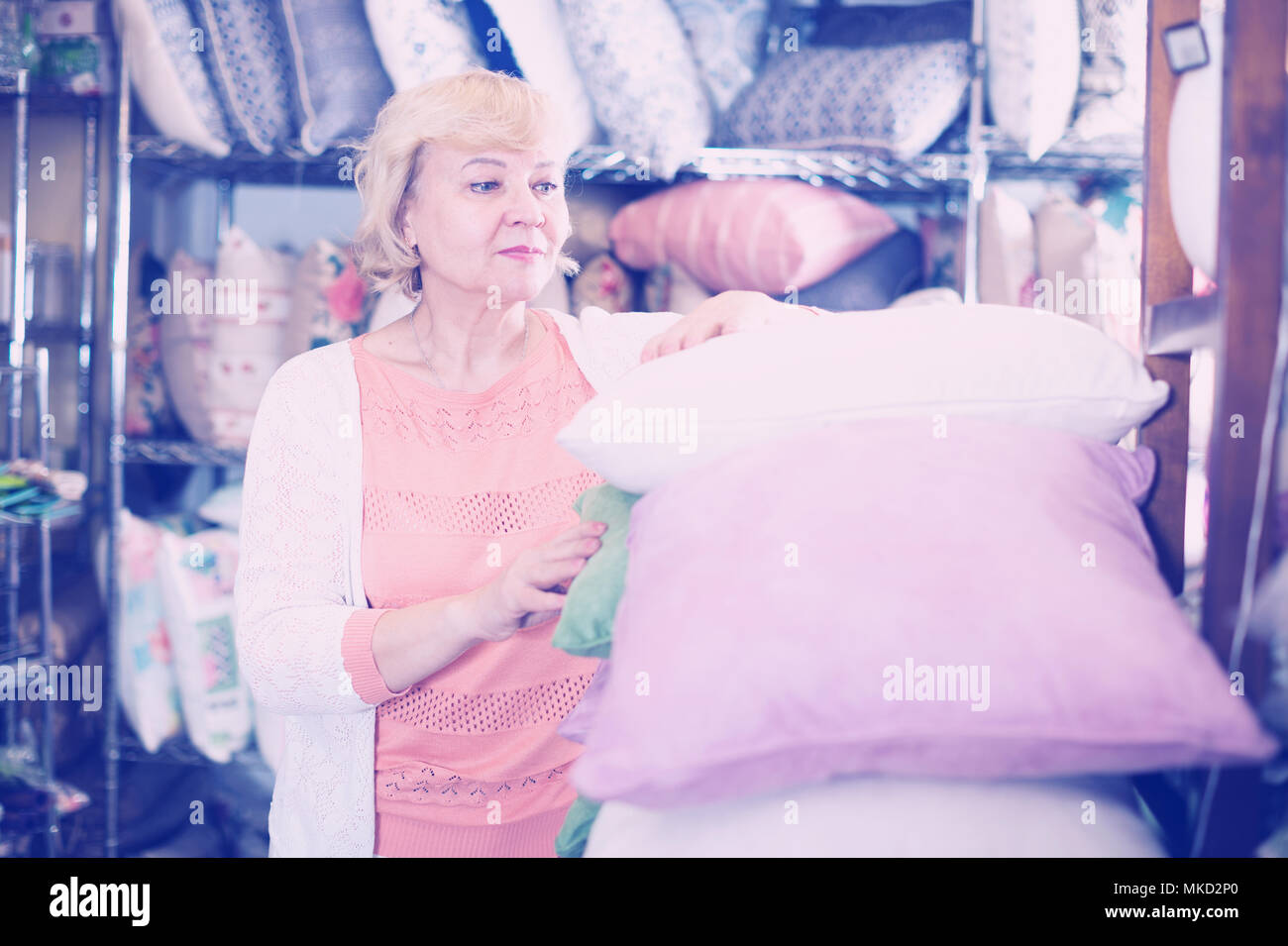 mature woman purchaser holding soft pillows in the textile sho - Stock Image