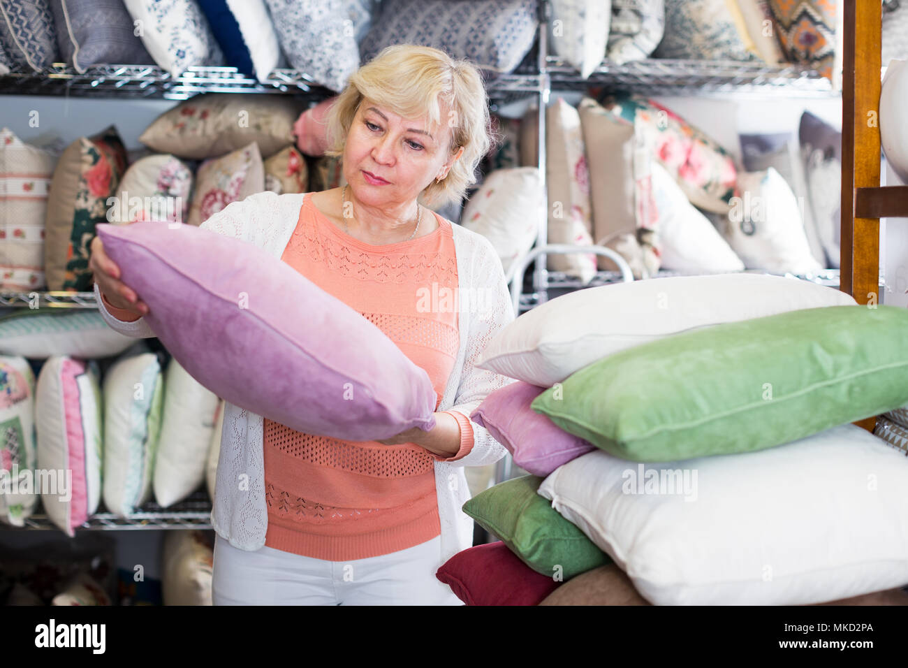 mature woman purchaser holding soft pillows in the textile shop - Stock Image