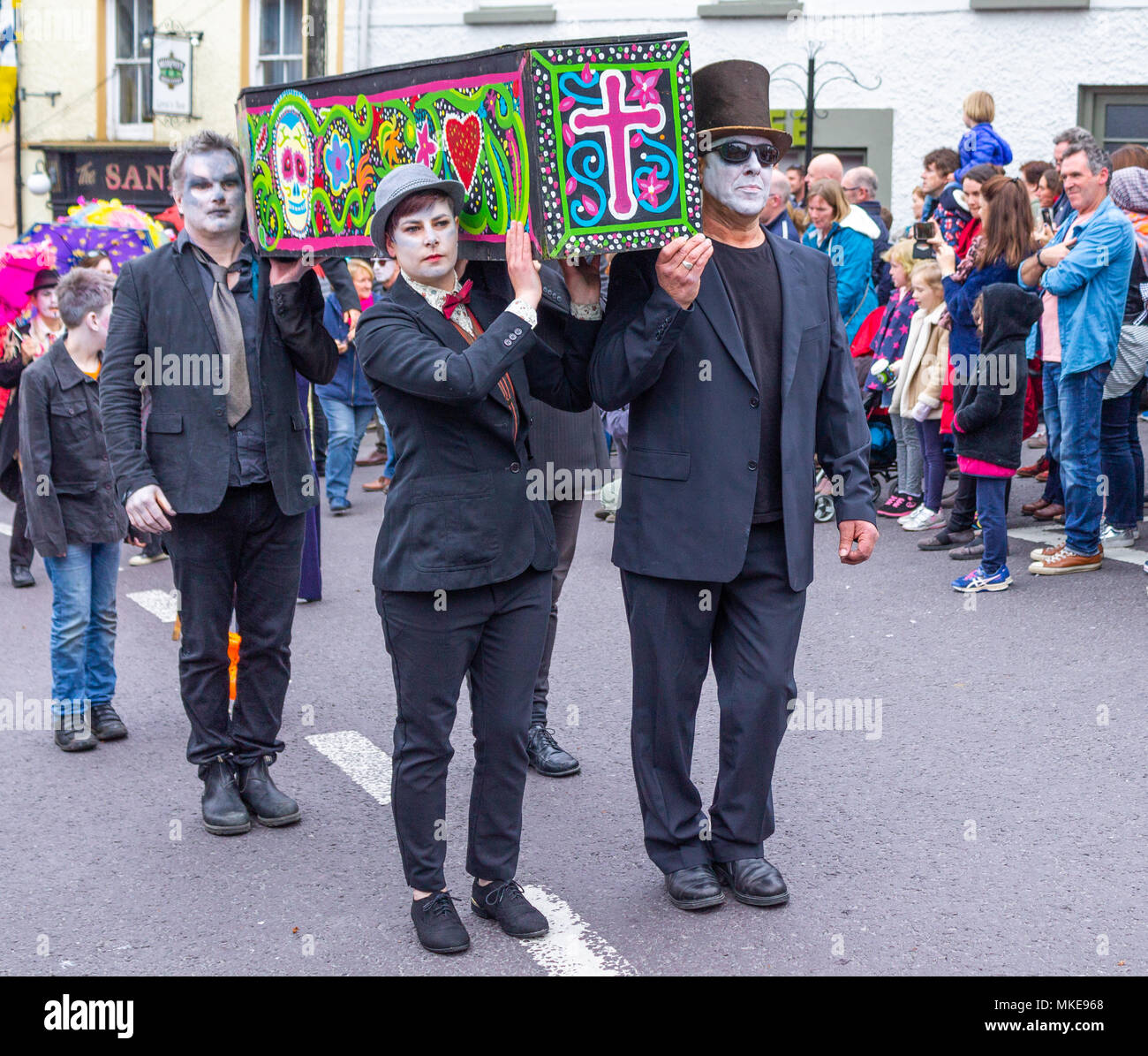 brightly-painted-coffin-and-street-performers-makeup-with-skull-faces-parading-through-the-street-as-part-of-a-music-festival-celebration-in-ireland-MKE968.jpg
