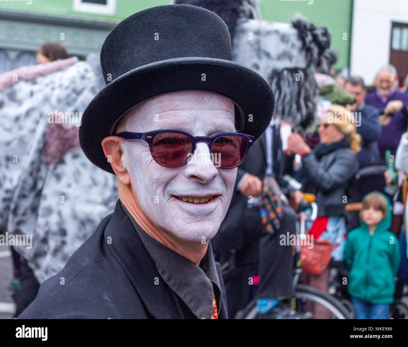 man-with-face-makeup-of-all-white-with-sunglasses-and-black-costume-taking-part-in-a-jazz-festival-street-procession-and-party-in-ballydehob-ireland-MKE986.jpg
