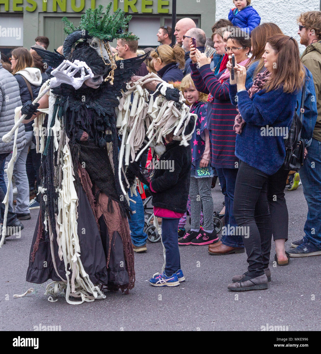 colourfully-dressed-street-performer-part-of-a-jazz-festival-procession-dressed-up-as-a-witch-dancing-in-the-street-of-ballydehob-ireland-MKE996.jpg