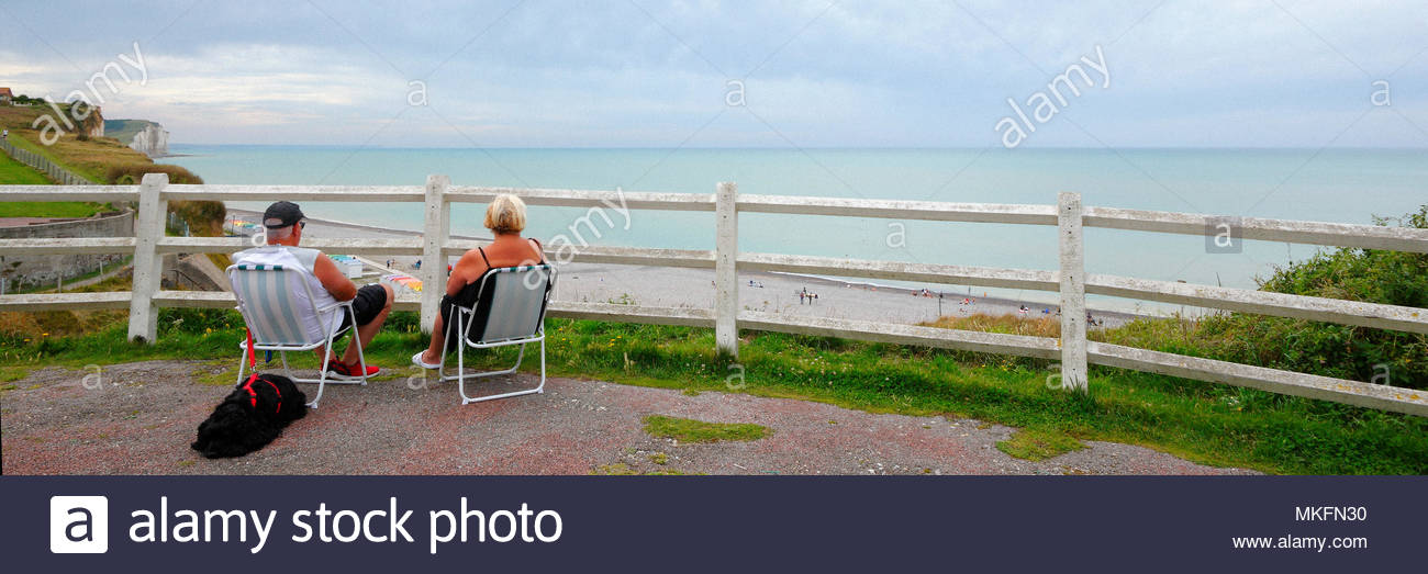 Senior Couple Accompanied By Their Dog And Sitting On Camping Chairs To  Watch The Sea And