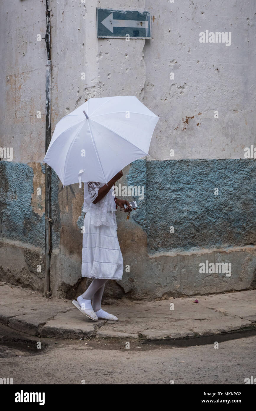 Female Observant Of The Santeria Religion, Dressed In White And Holding An  Umbrella That Is