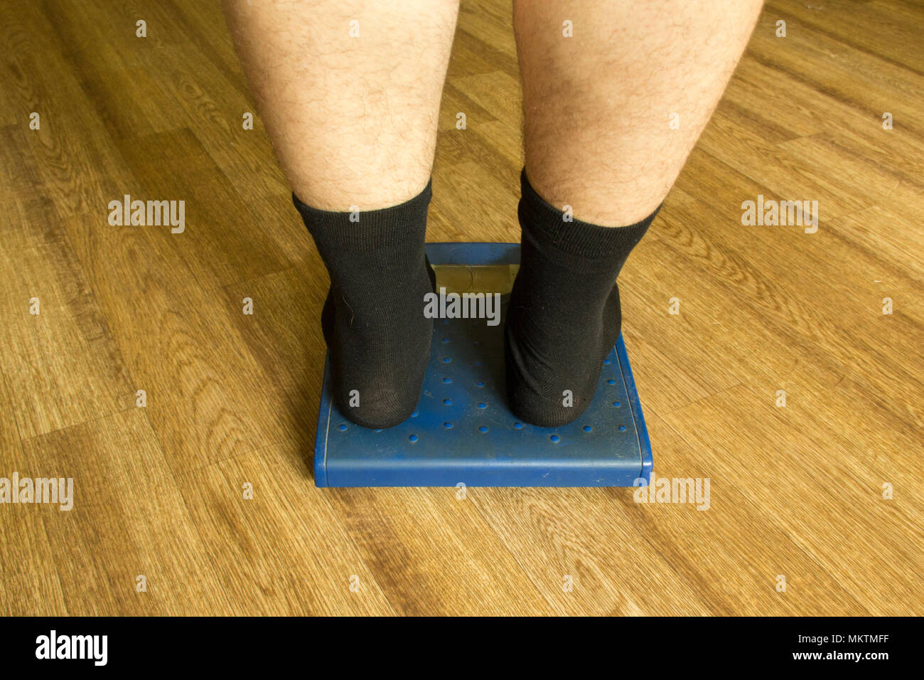 Men's legs in black socks stand on the mechanical scales of blue color (rear view) Stock Photo