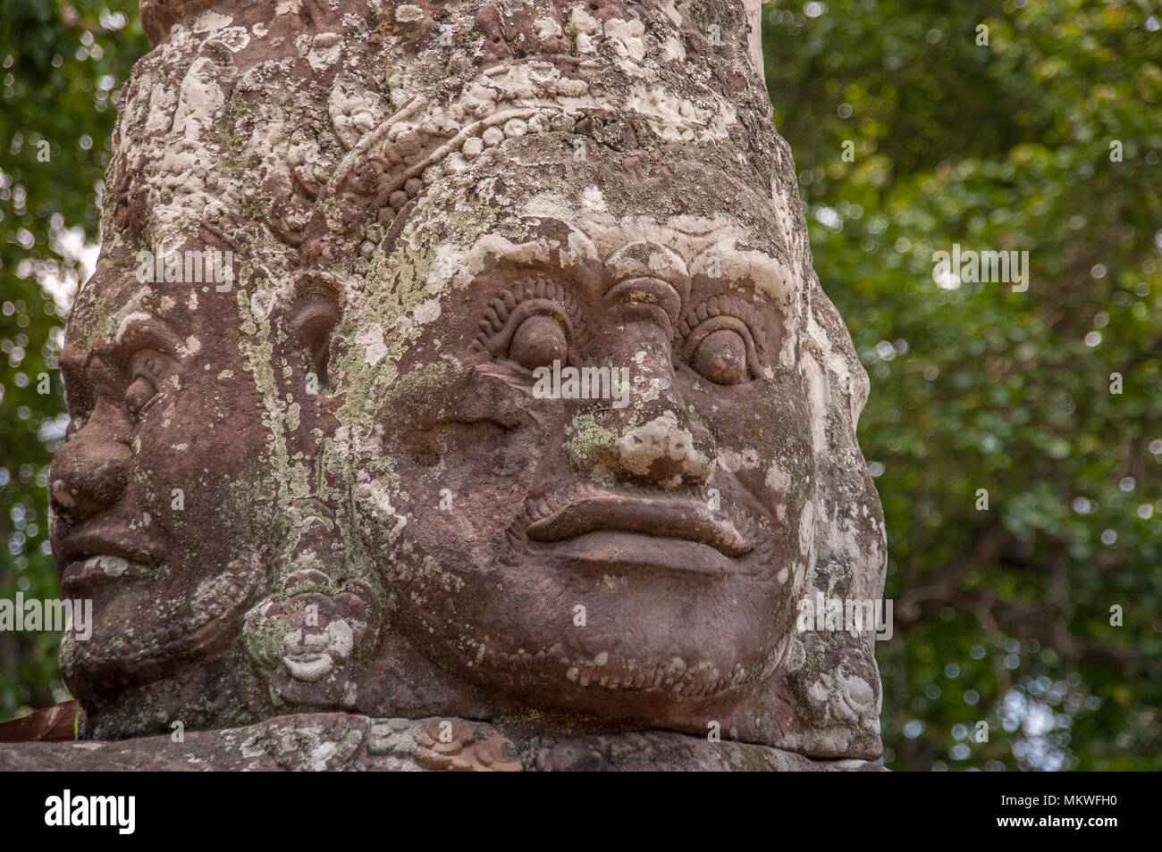 Giant Head With 4 Faces At Bayon Shows Classic Khmer Art And Architecture Only 2 Can Be Seen Against A Soft Green Background Of Trees