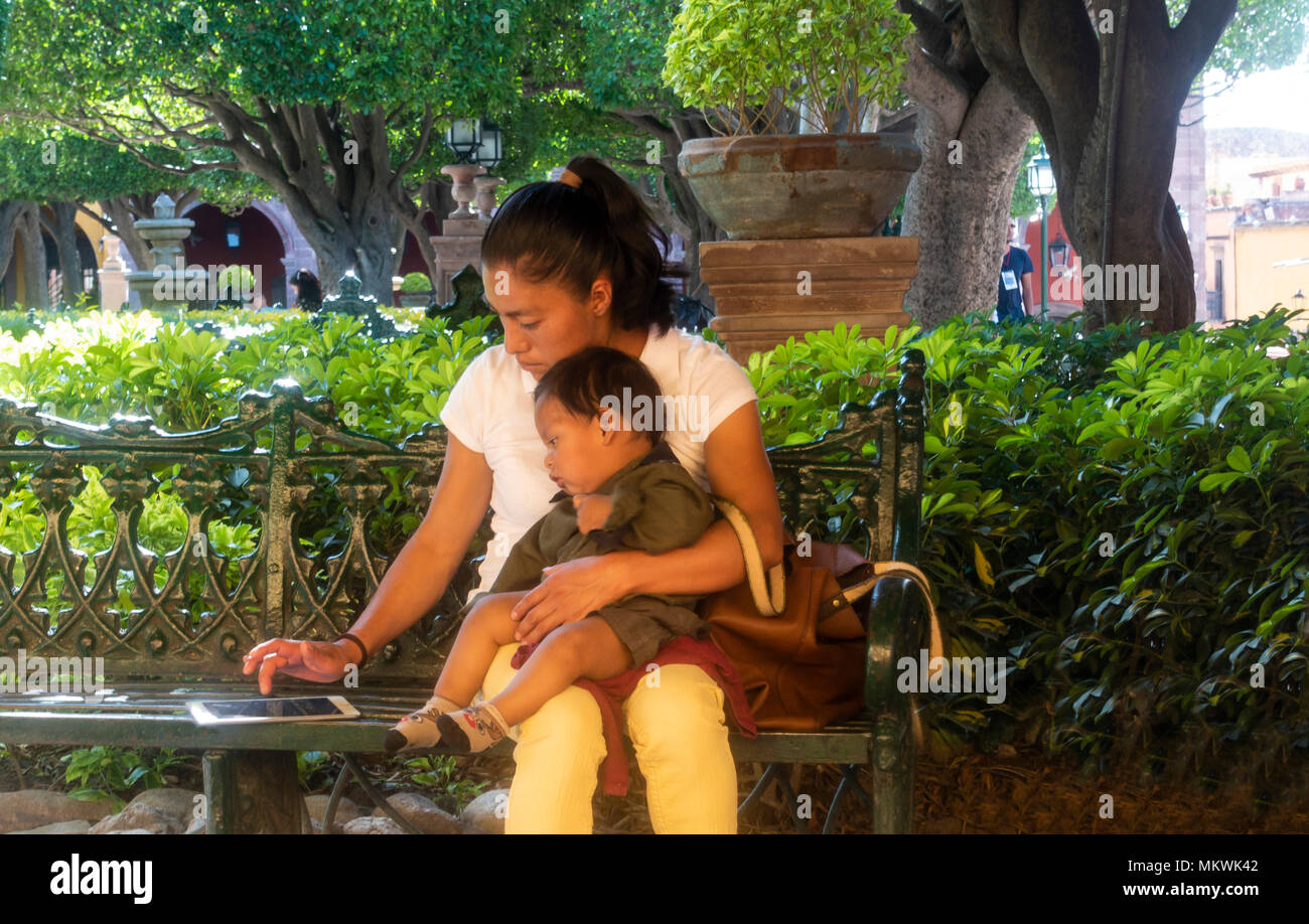 In San Miguel de Allende, Mexico, a young mother with a male child plays on an iPad sitting on a metal bench in the Jardin. - Stock Image