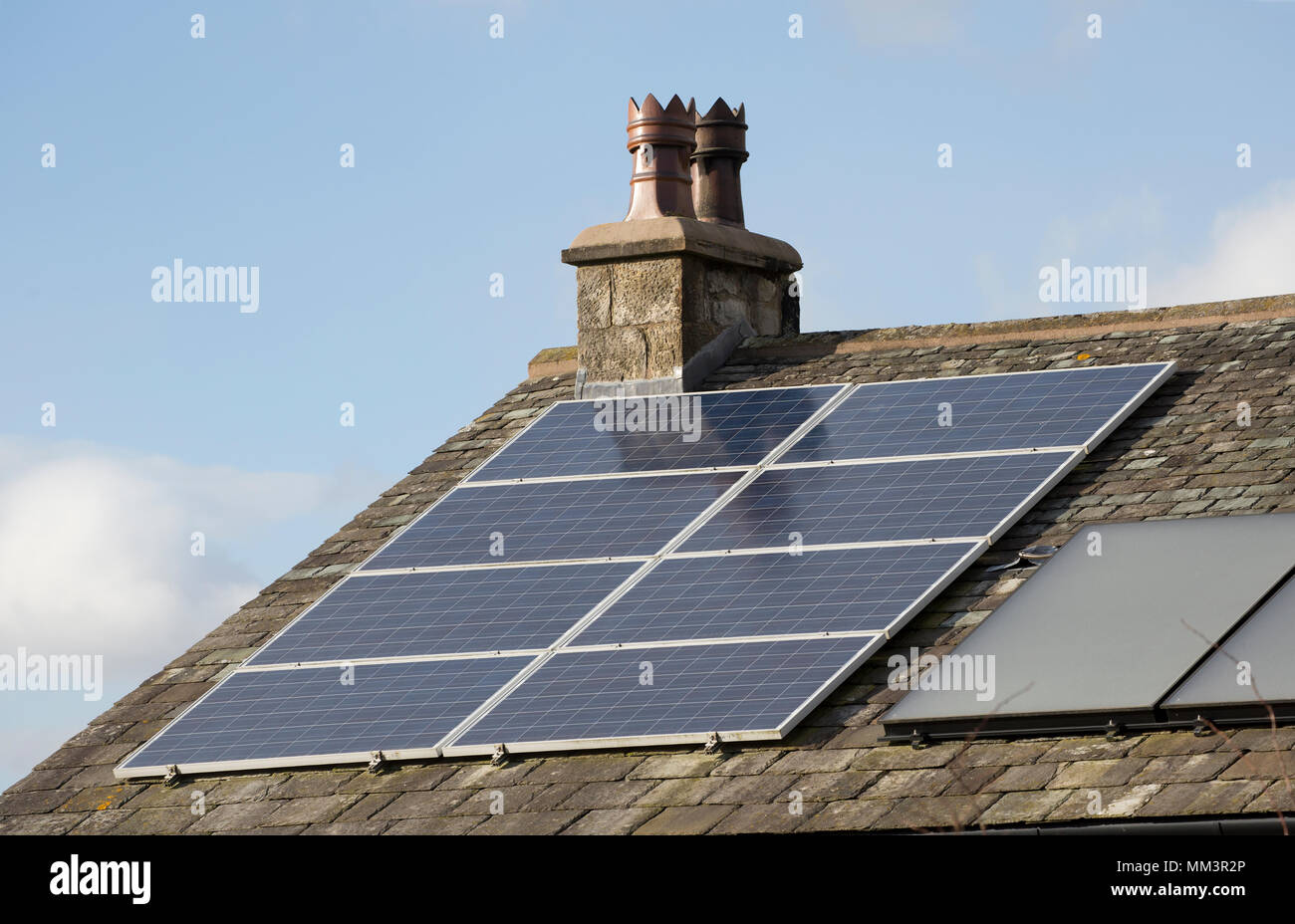 Solar panels on the roof of a house next to traditonal chimney pots. North Dorset England UK - Stock Image