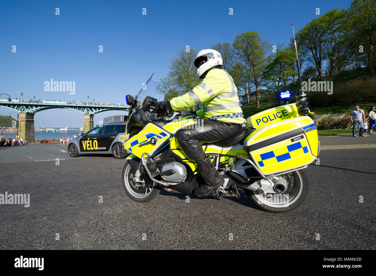 One of the police motorcycle riders stops traffic on stage 3 of the Tour De Yorkshire cycle race 2018 passes through Scarborough in North Yorkshire - Stock Image