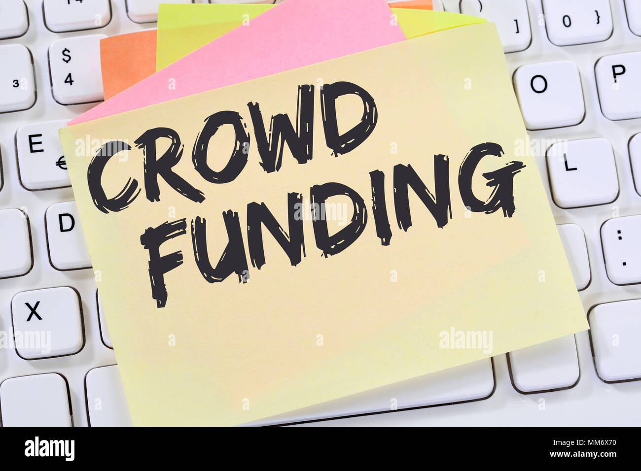 Crowd funding crowdfunding collecting money online investment internet business concept note paper desk computer keyboard - Stock Image