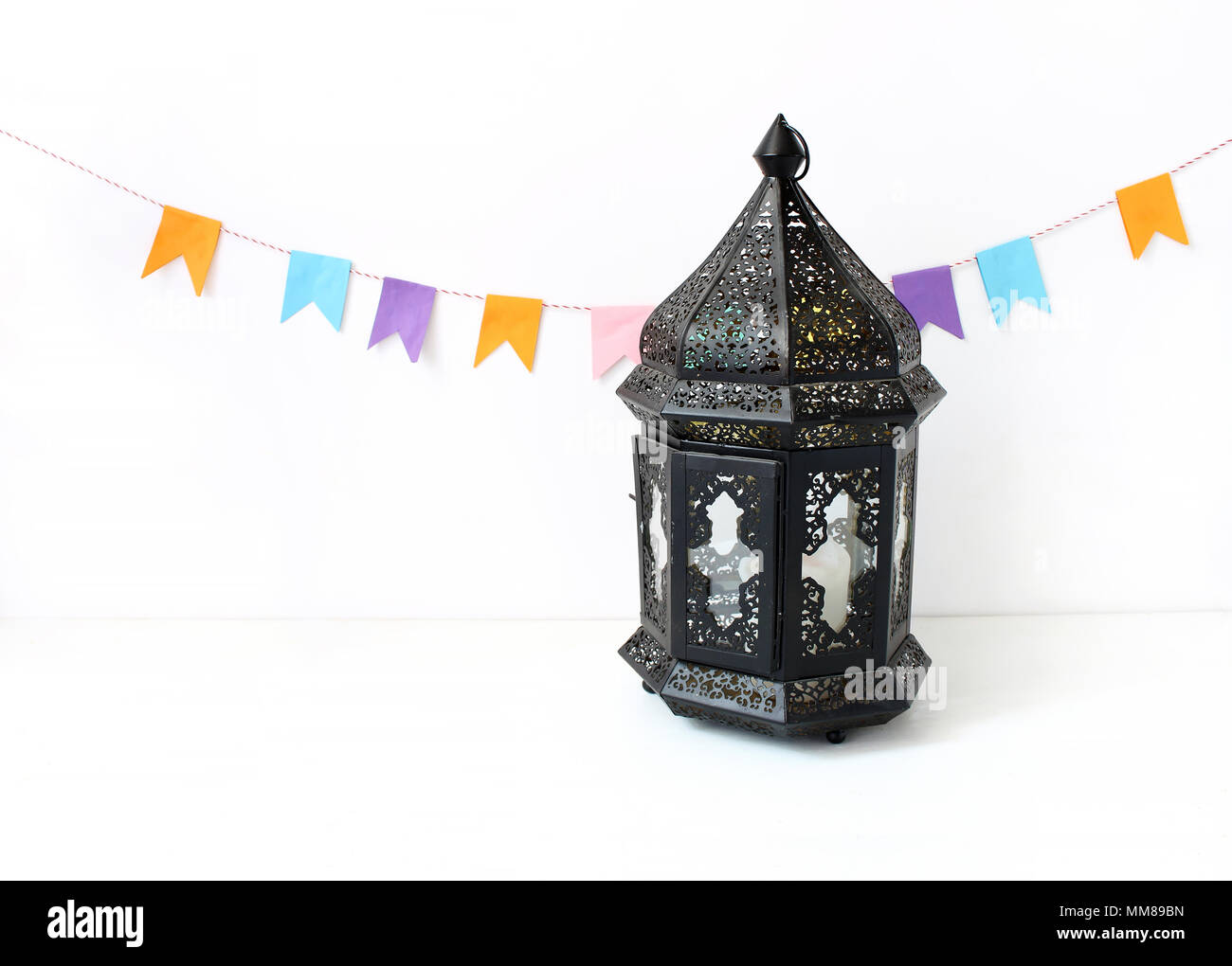 Good Night Sky Party Eid Al-Fitr Decorations - ornamental-dark-moroccan-arabic-lantern-on-the-white-table-party-decoration-string-of-colorful-paper-flags-greeting-card-for-muslim-holiday-ramadan-kareem-festive-background-MM89BN  Trends_484150 .jpg