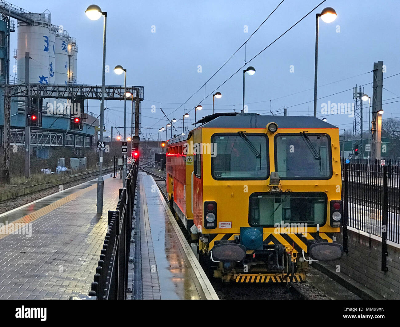 GoTonysmith,@HotpixUK,Warrington Bank Quay station at dusk,Cheshire,England,UK,winter,at platform,in station,yellow,tamper,Railway,Network Rail,Networkrail,track maintenance,engine,vehicle,at,night,nighttime,night time,BR,British Rail,Railtrack,Network Rail Maintenance Engine,DMU,Track Repair,Red Signal,MPV,investment programme,GRIP,Governance for Railway Investment Projects,Railway Investment Projects,measuring,Running the railway,infrastructure monitoring train,maintaining and renewing track,necessary maintenance