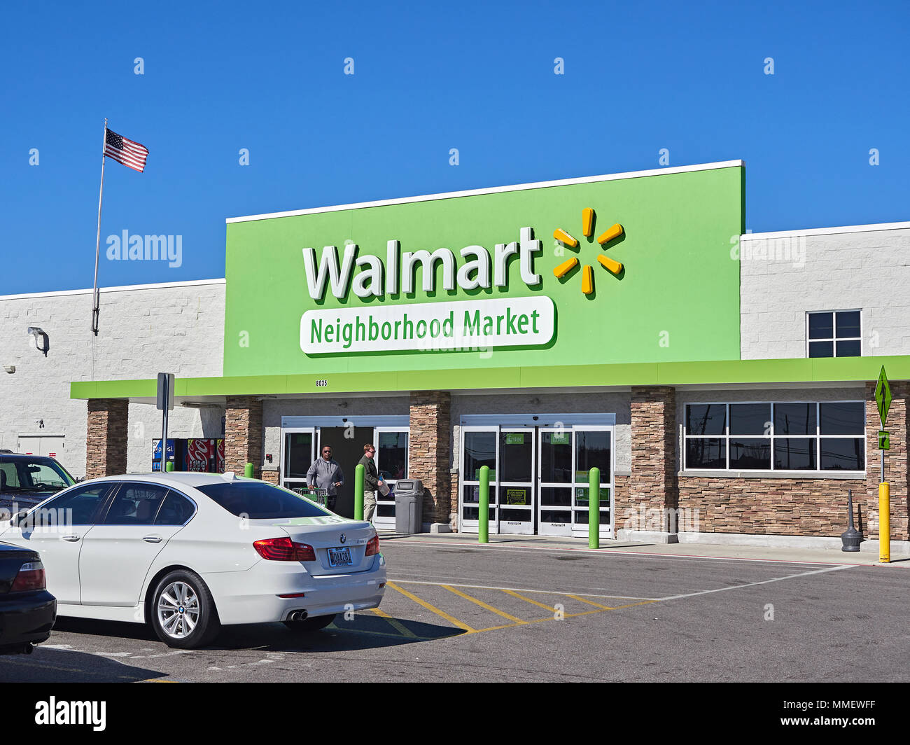 Exterior entrance to Walmart Neighborhood Market or grocery store showing the corporate logo and sign or signage in Montgomery Alabama, USA. - Stock Image
