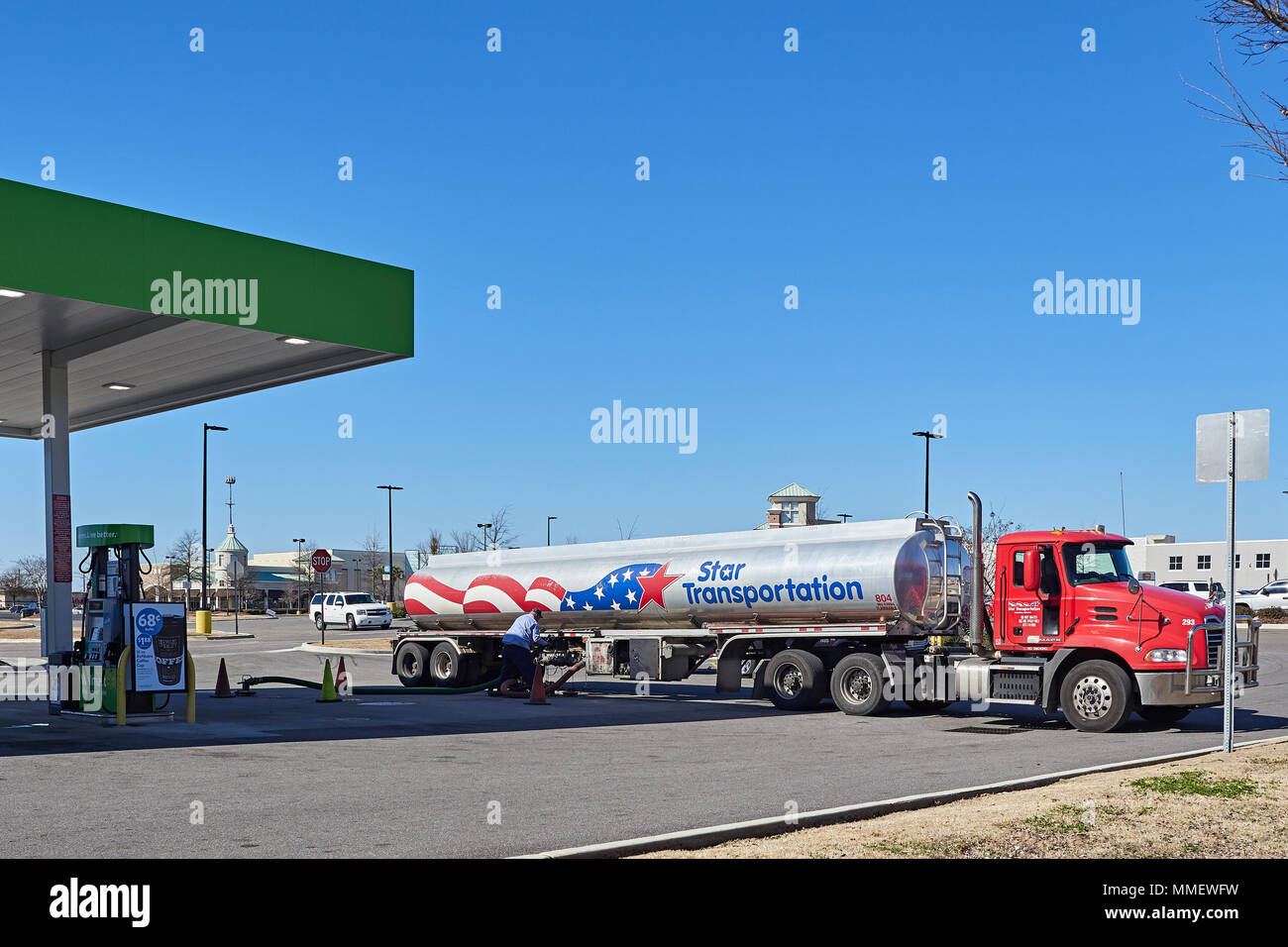 Gasoline or petrol tank truck supplying or off loading fuel at a retail gas station in Montgomery Alabama, USA. - Stock Image