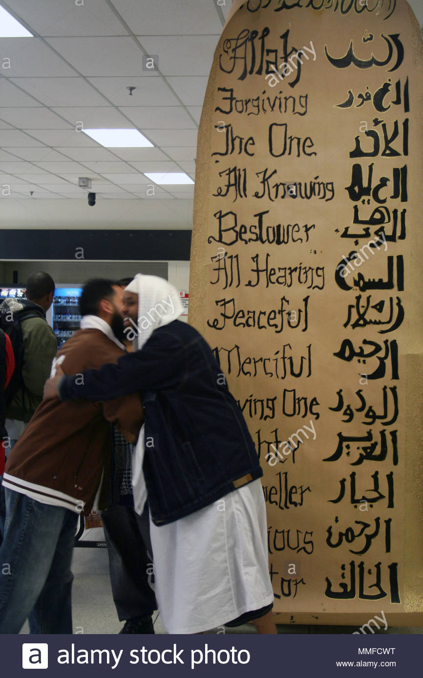 muslim men embrace by a banner with the many names of allah during