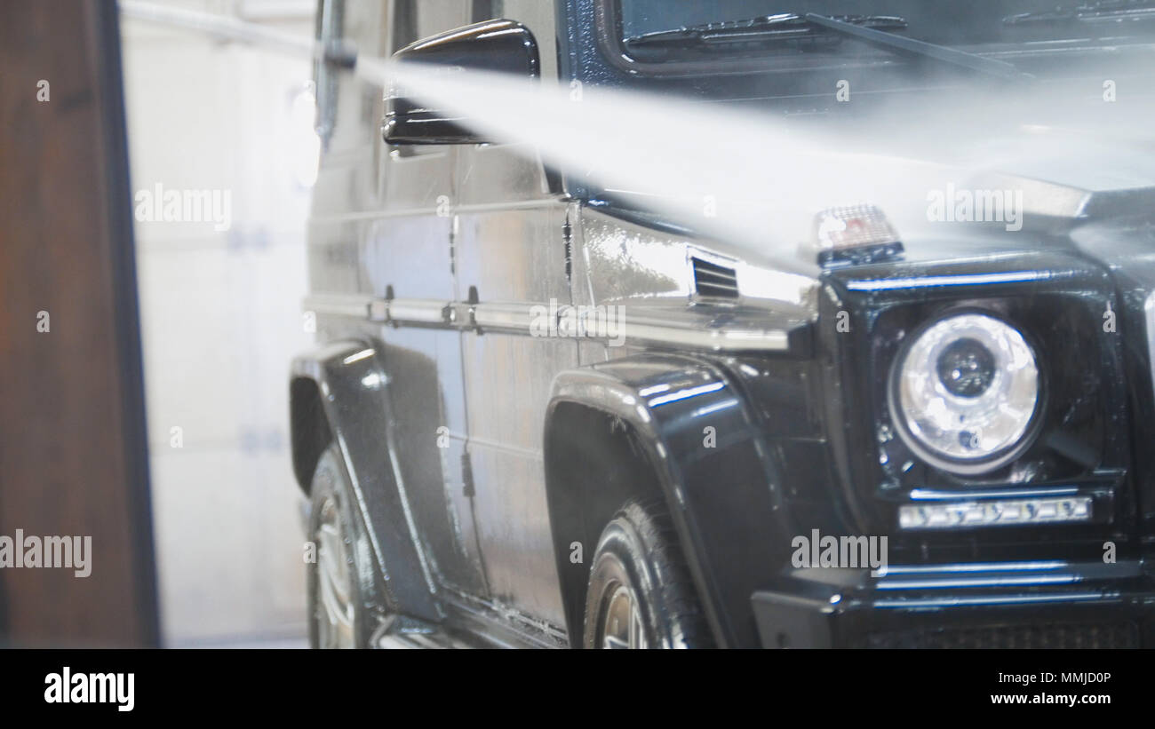 Washing The Suv Car In The Suds By Water Hoses In Auto Service