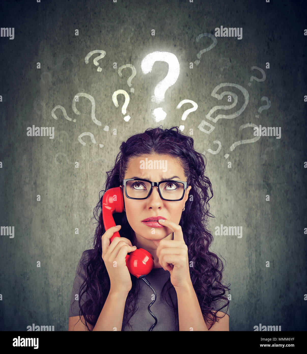 Misunderstanding and distant call. Upset worried confused woman talking on a phone has many questions isolated on gray background. Stock Photo