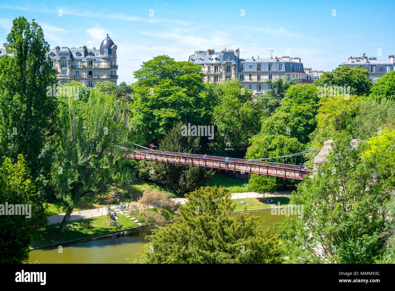 A bridge in parc des buttes chaumont with Parisian haussmann architecture, paris, france Stock Photo