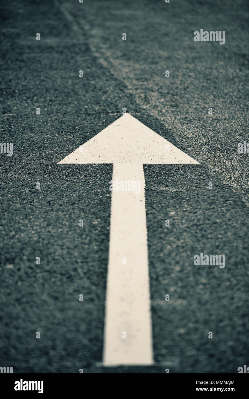 White direction arrow on a tarmac road - Stock Image