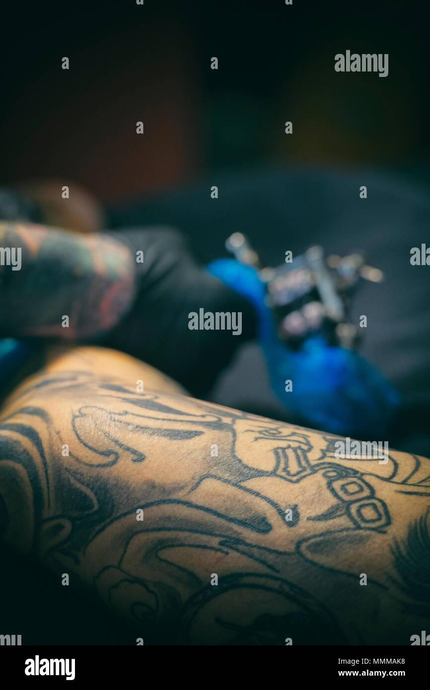Tattoo artist applying a design to a man's leg - Stock Image