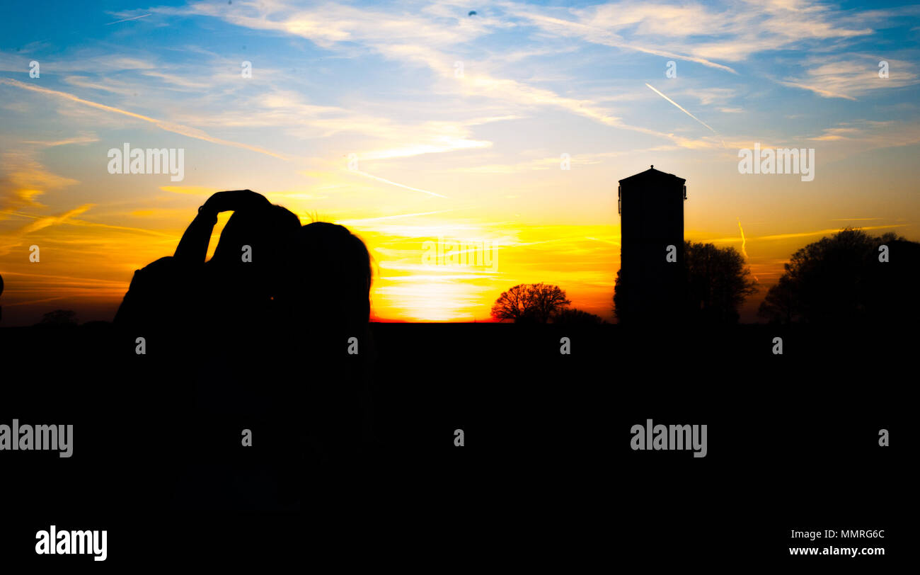Silhouette of romantic couple kissing during the sunset time Stock Photo