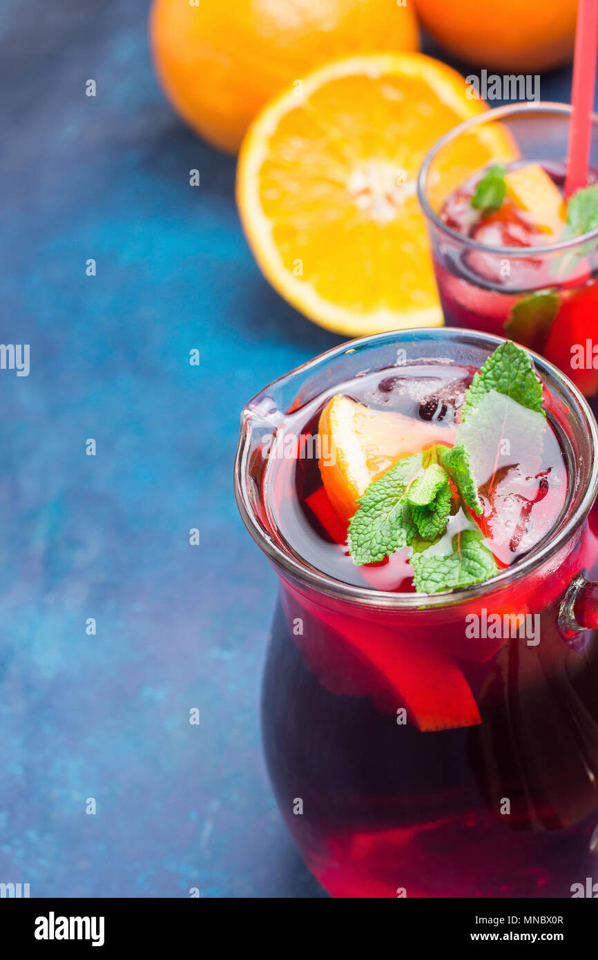 Refreshing Non-Alcoholic Spanish Sangria from Variety of Fruits Orange Citrus Pomegranate Grapes Berries and Fresh Mint in Pitcher and Tall Glass on B - Stock Image