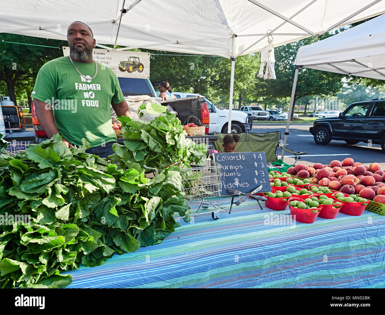African-American male farmer selling fresh southern produce at a farmer's market in Montgomery Alabama, USA. - Stock Image