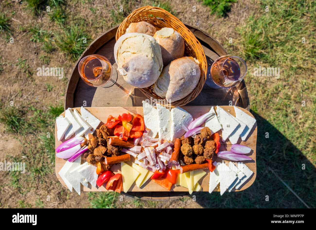 Food plate with traditional Eastern Europe food: onions, bread, cheese, sausages, meatballs and red wine in glass, in nature - Stock Image
