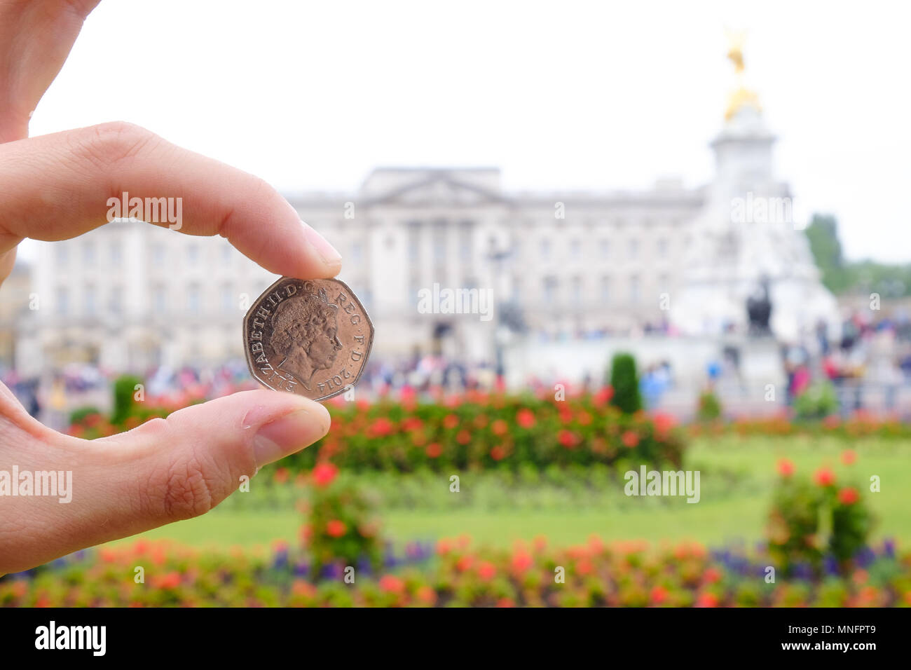 English coin picturing the Queen in front of Buckingham Palace. Focus on the coin. Artistic interpretation. - Stock Image