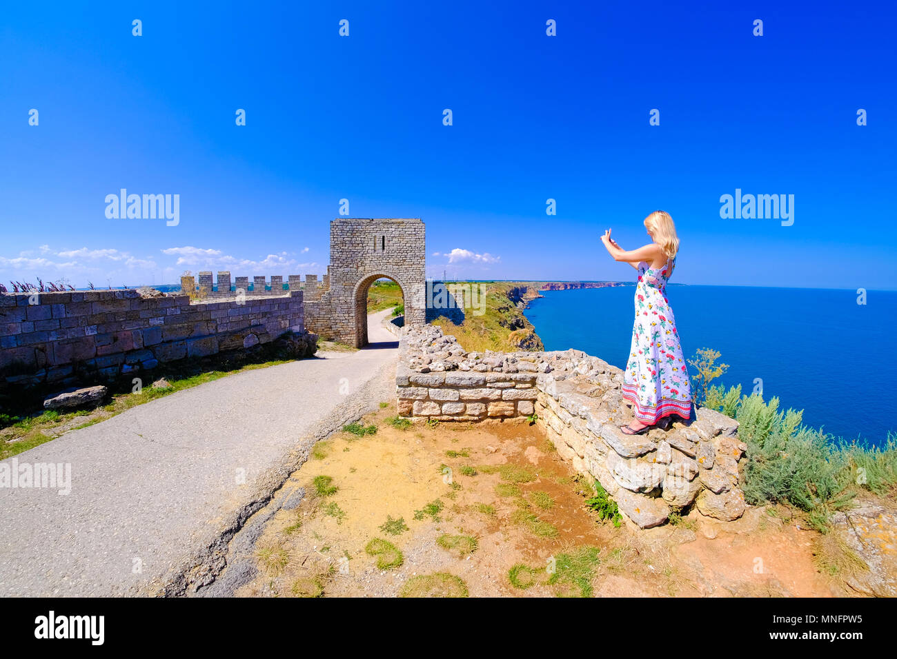 Woman taking pictures at Cape Kaliakra, Bulgaria, Black Sea. Old abandoned fortress by the sea. Important tourist attraction. - Stock Image
