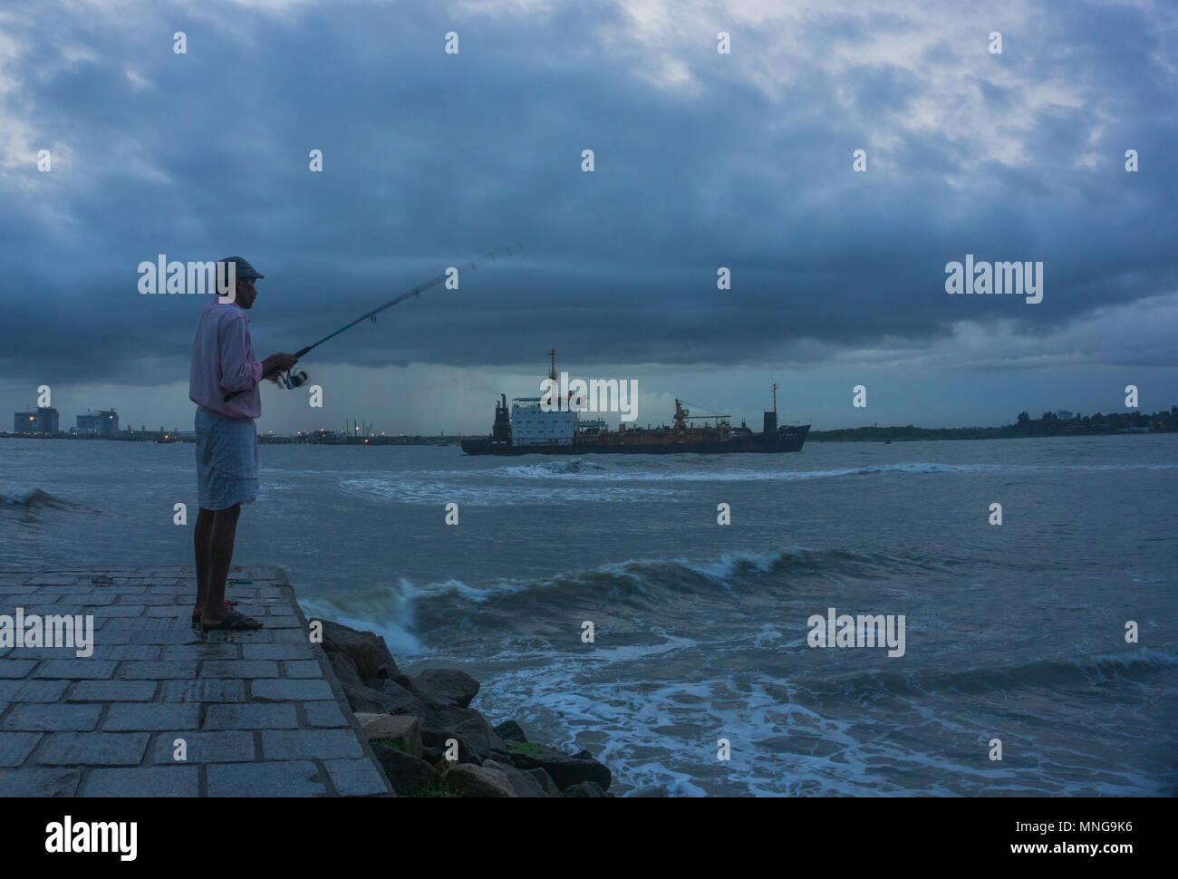 A man angling at Fort Kochi beachfront - Stock Image