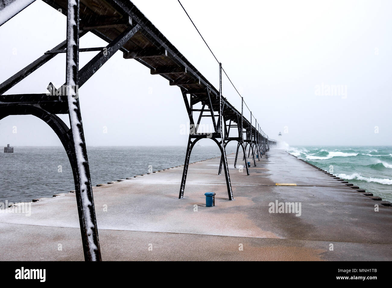 Pier and lighthouse in showstorm, Manistee, Michigan, USA. - Stock Image
