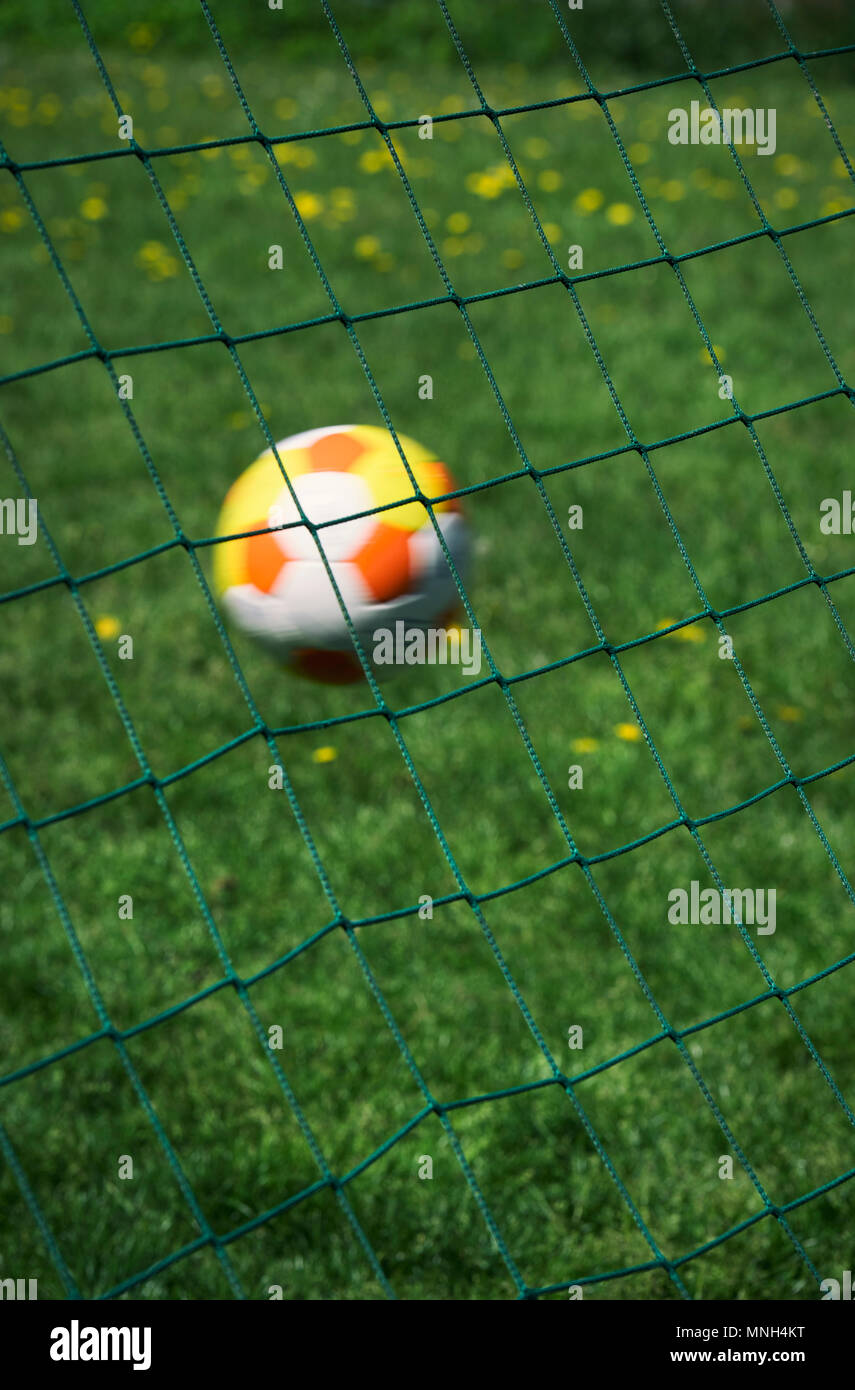 Football hitting the back of a goal net - Stock Image