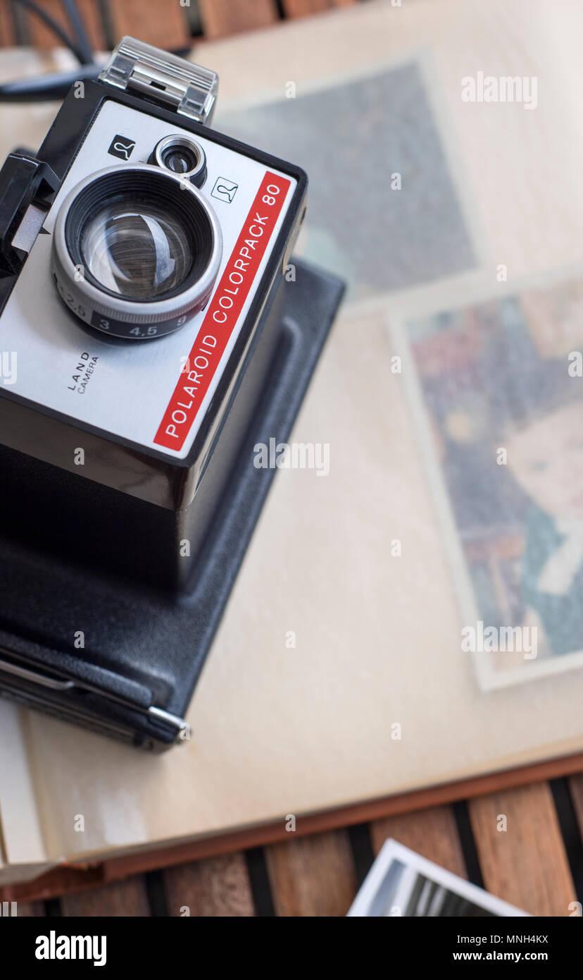 Old Polaroid camera on top of a photo album - Stock Image