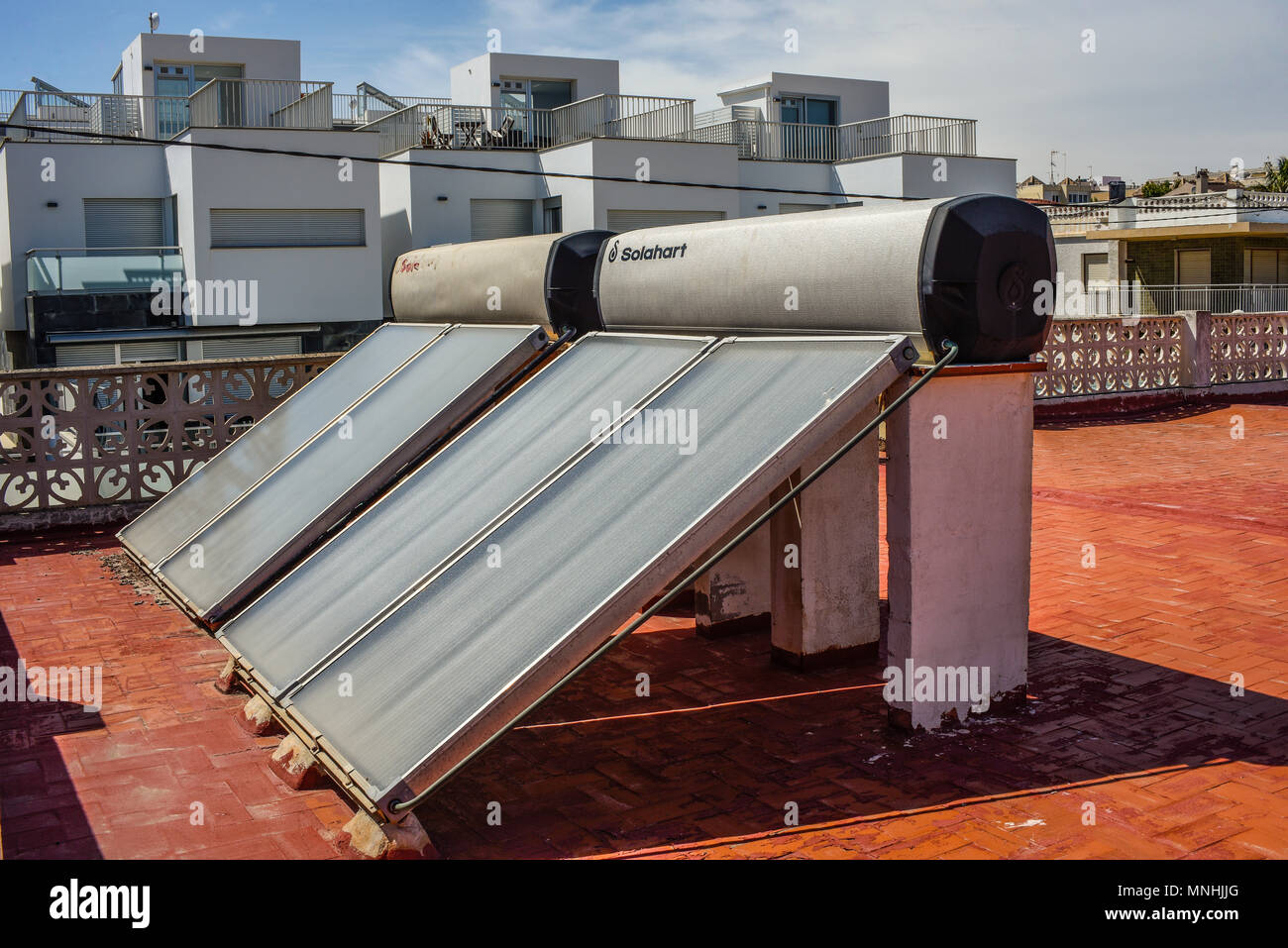 Solahart water heating solar panels. Energy cost saving environmentally friendly hot water system. Flat roof mounted at an angle. Storage - Stock Image