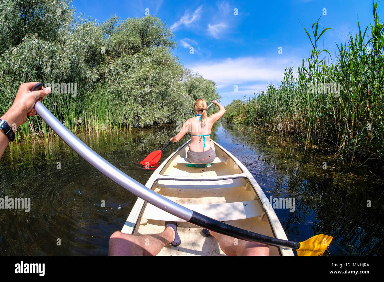Sailing into Danube Delta channels in a boat - Stock Image