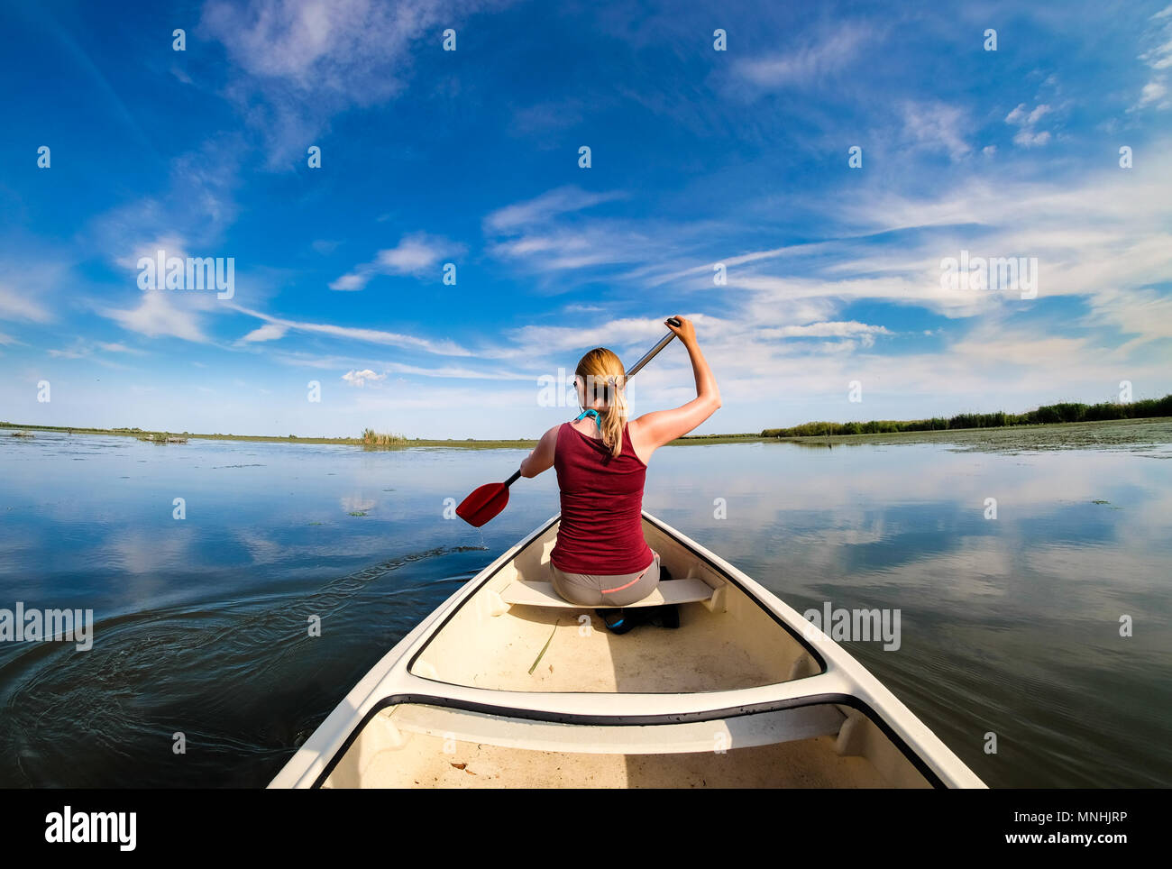 Woman exploding Danube Delta in a boat - Stock Image