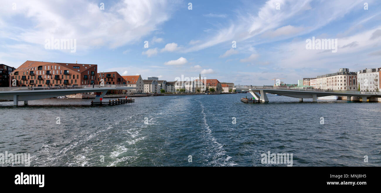 The pedestrian and cyclist bridge, the Inner Harbour Bridge, the Kissing Bridge, connecting Nyhavn and Christianshavn is open for a departing vessel. - Stock Image