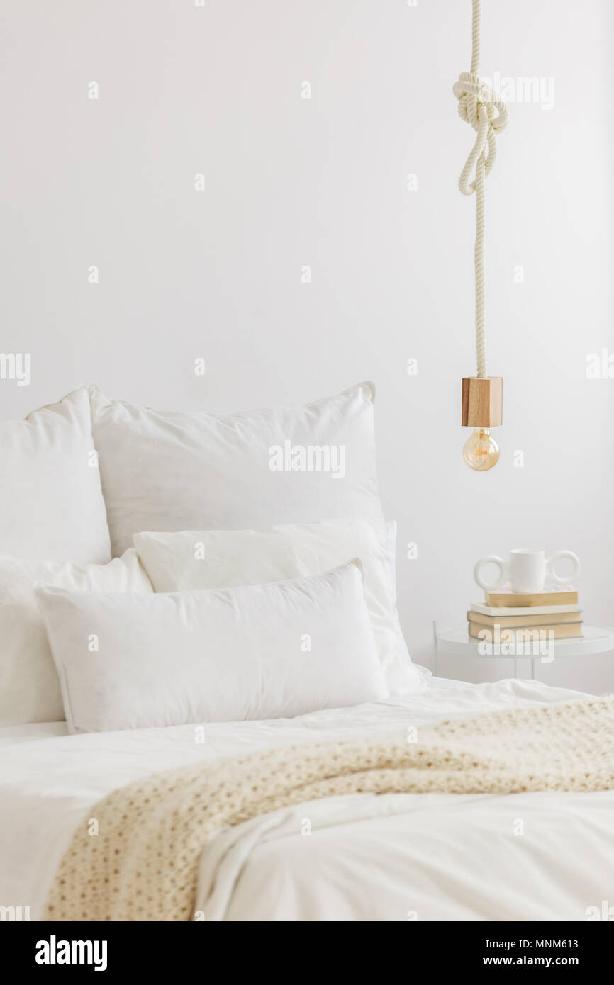Close Up Photo Of Gold Bulb Lamp Hanging Above Bed With White Bedsheets And  Knit Blanket In Bedroom Interior