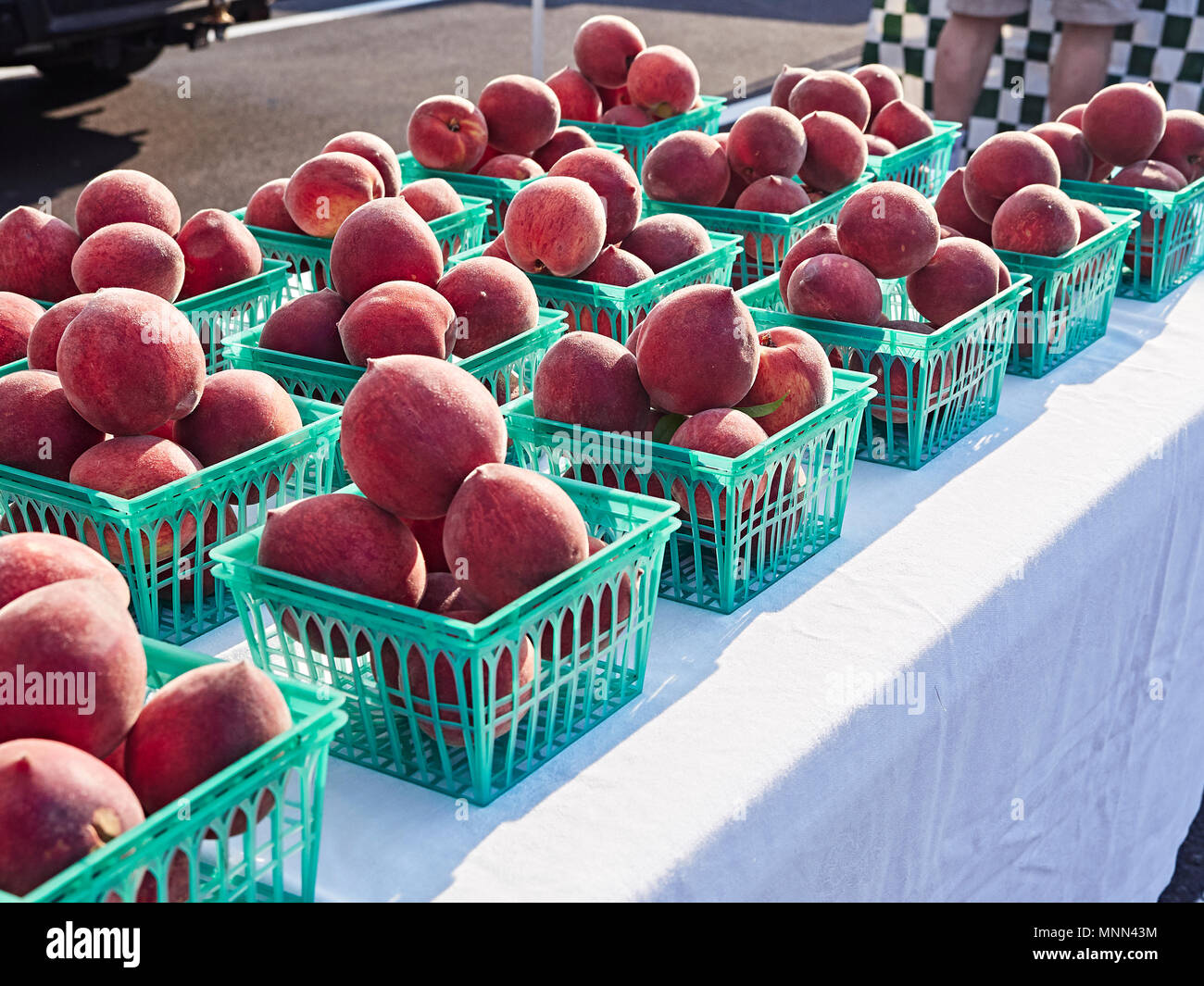 Ripe, fresh picked Chilton County peaches on display in baskets at a roadside farmers market in Alabama, USA. - Stock Image