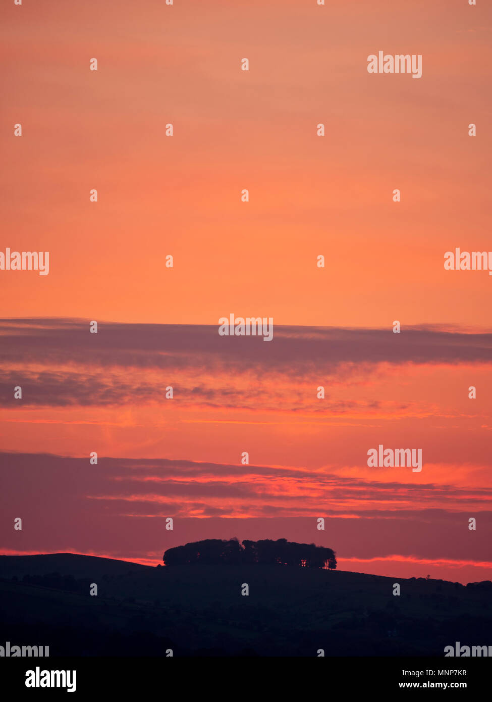 Peak District, Derbyshire, UK. 18th May, 2018. UK Weather: spectacular sunset over the ancient woods Hazleton Clump Cairn near Thorpe taken from Ashbourne Derbyshire, Peak District National Park Credit: Doug Blane/Alamy Live News - Stock Image