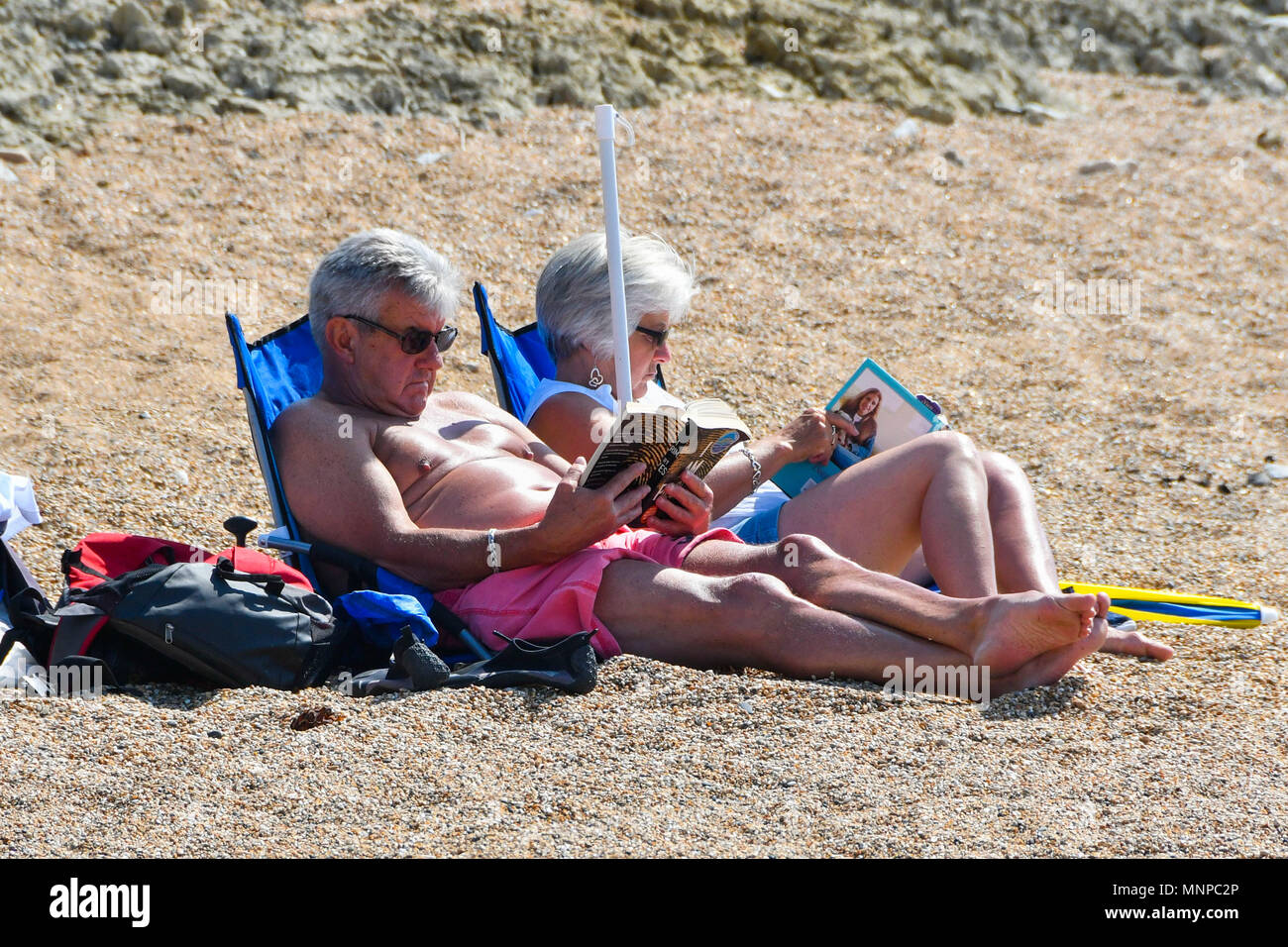 Burton Bradstock, Dorset, UK.  19th May 2018. UK Weather.  Visitors on the beach enjoying the warm sunshine at Burton Bradstick in Dorset.  Picture Credit: Graham Hunt/Alamy Live News Stock Photo