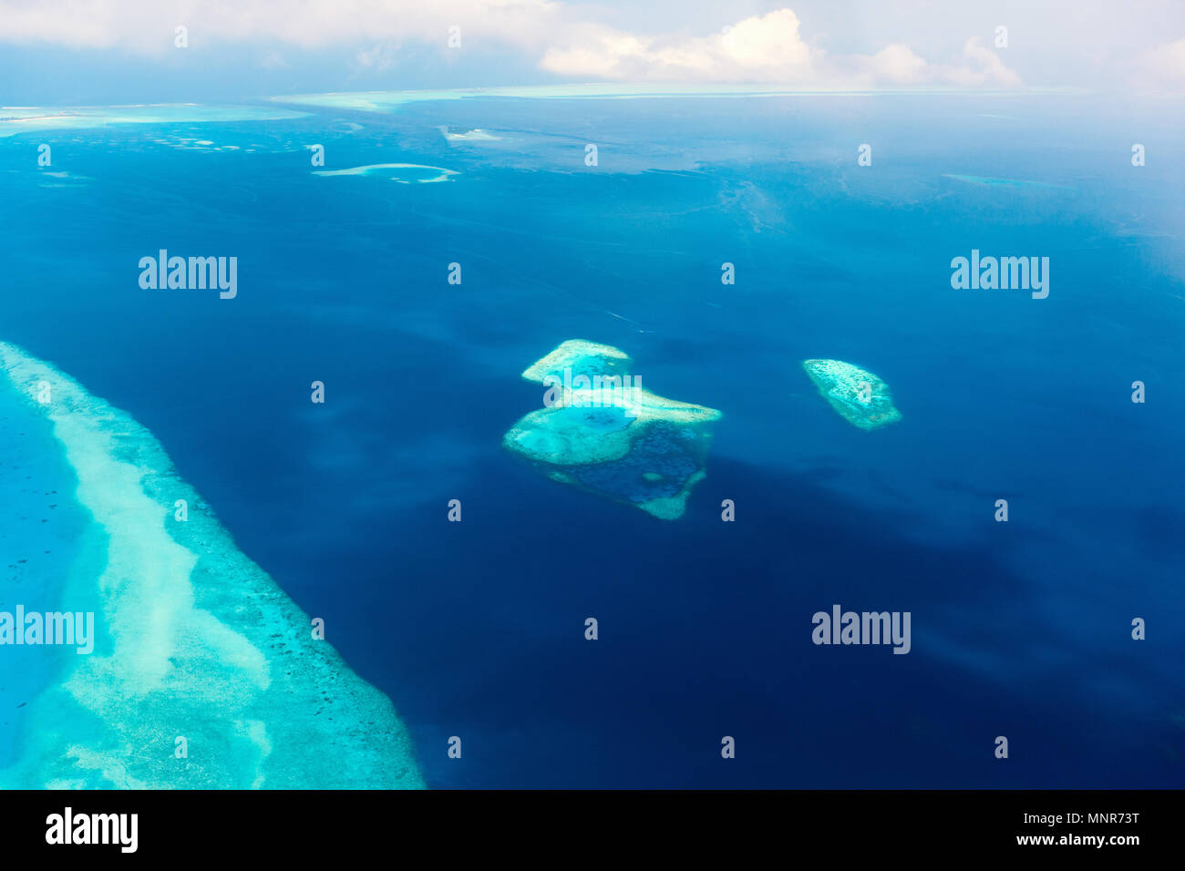 Aerial view of Maldives atoll and reefs seen from a sea plane - Stock Image