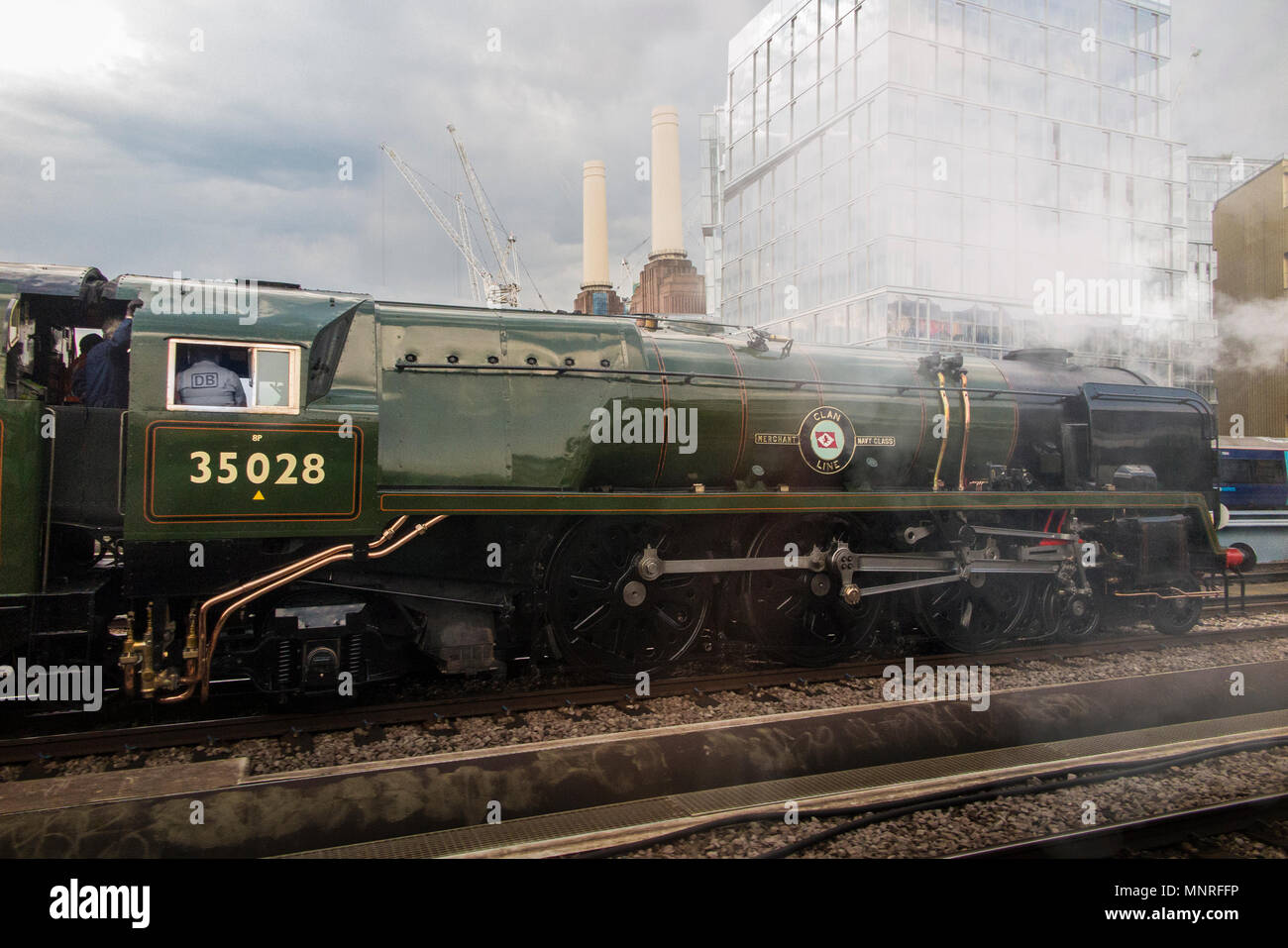 A steam engine locomotive  on it's way past the iconic Battersea Power Station in Central London - Stock Image