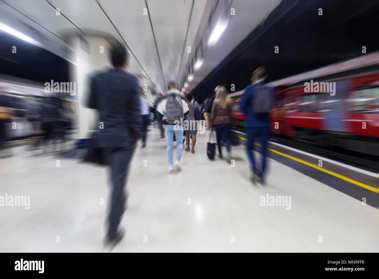 Commuters racing to work on the platform of a London station once the train pulls in - Stock Image