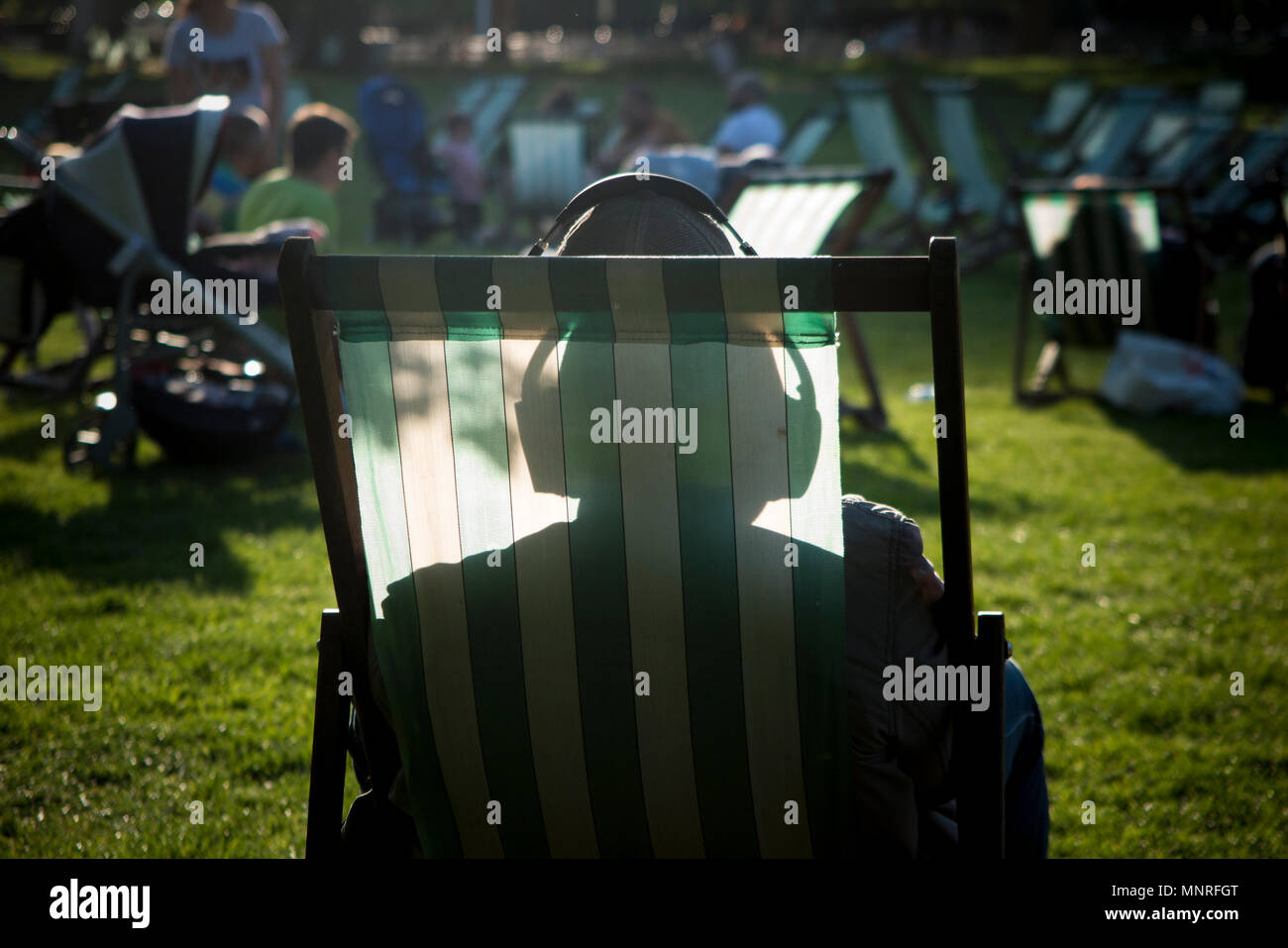A man relaxes in the sunshine, listening to music with headphones, silhouetted against the striped canvas of the deck chair - Stock Image