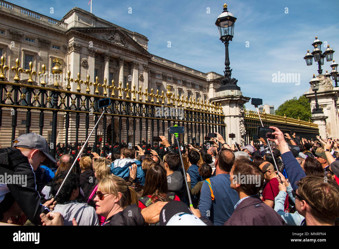 Taking photographs using a selfie stick at an event at Buckingham Palace on a hot summers day - Stock Image