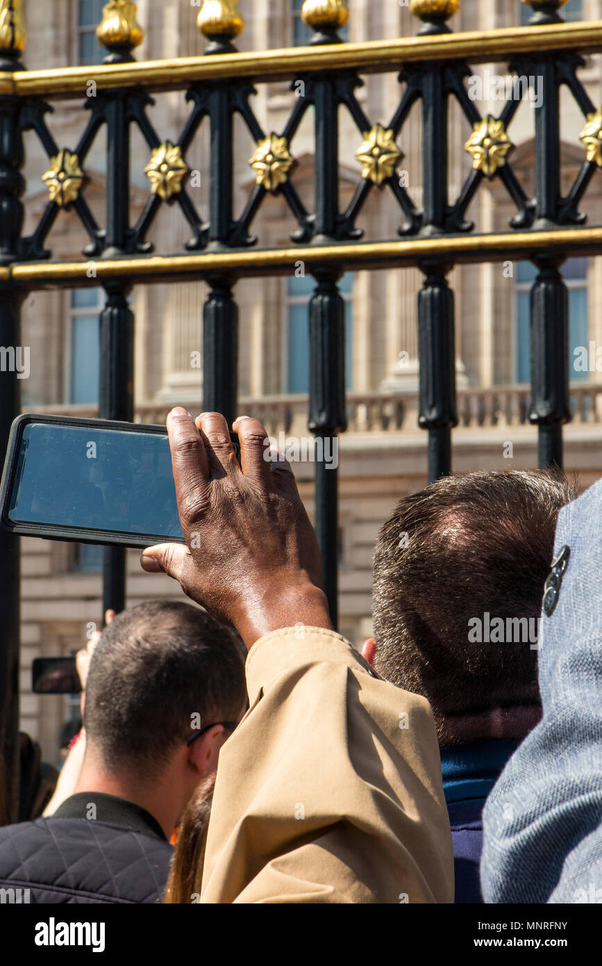 Crowds of people with phones take selfies and pictures of an event at Buckingham Palace - Stock Image