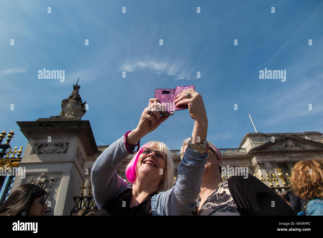 Two ladies with pink hair take a selfie and pictures of an event at Buckingham Palace - Stock Image